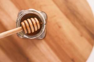 färsk honung med skopa på träbord foto