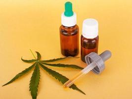 medicinskt cannabisextrakt som innehåller thc och cbd, medicinsk hampolja och grönt blad på gul bakgrund foto