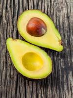 halverad avokado med kärna isolerad på en träbakgrund foto