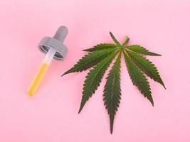 cannabisblad och pipett med extrakt av thc-koncentrat på rosa bakgrund foto