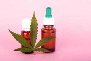 hampolja för medicinskt bruk, flaskor med medicinskt cannabisextrakt på rosa bakgrund foto