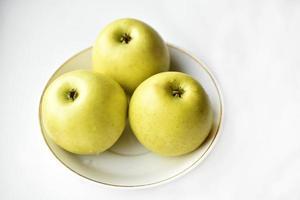 tre gröna äpplen på en vit platta foto