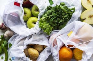 frukt och sommargrönsaker i återanvändbara miljövänliga påsar på marmorbakgrund. noll avfallshopping. ekologiska koncept. foto