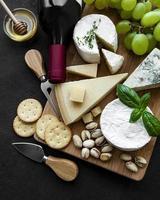 olika typer av ost, druvor och vin på ett träbord foto