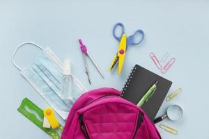 skolmaterial platt låg med rosa ryggsäck foto