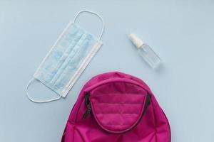 rosa ryggsäck med mask och handdesinfektionsmedel foto