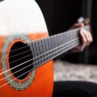 hand på greppbrädan av akustisk gitarr i orange färg foto