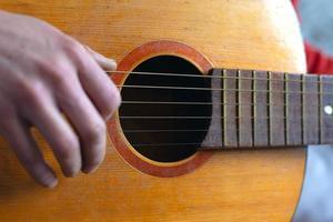 fingrarna spelar strängarna på en klassisk akustisk gitarr foto