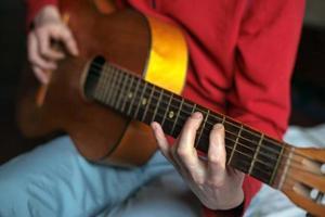 virtuos gitarrist som spelar sin akustiska gitarr foto