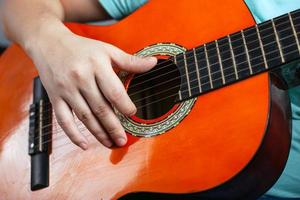 kille som spelar en akustisk sexsträngad gitarr foto