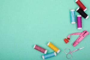 sysats tillbehör med färgglada trådar, nålar, stift, sax på grön bakgrund foto