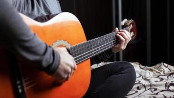 flicka som spelar en akustisk sexsträngad gitarrnärbild foto