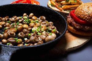 champignonsvamp i en svart panna och en saftig hamburgare foto