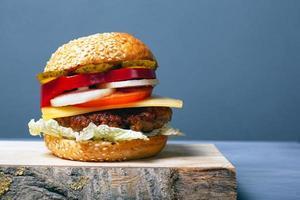 saftig hamburgare med kotlett, ost och grönsaker på en grå bakgrund med kopieringsutrymme foto