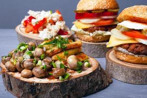 stekt potatis med svamp och saftiga köttburgare på trästubbar foto