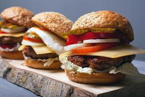 läckra hemlagade hamburgare på ett träställ på en grå bakgrund, sidovy foto