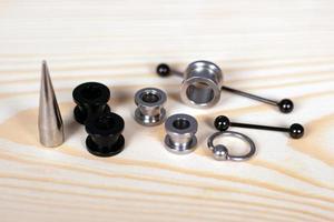 uppsättning tillbehör för piercing på en träskiva foto