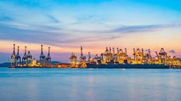 fraktfartyg som laddar last vid lastdockan på skymningstiden i singapore