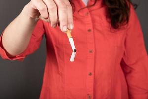 trasig cigarett i kvinnliga händer, sluta röka tecken foto