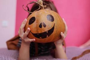 glad Halloween. flicka in med en snidningspumpa. lycklig familj förbereder sig för halloween. foto