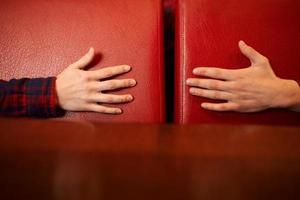 manliga och kvinnliga händer når varandra på en röd bakgrund. begreppet vård, stöd och kärlek. foto