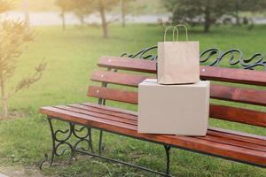 två paket på en bänk utomhus. take-out koncept foto