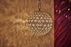 taklampa upplyst, elegant ljuskrona upplyst. rund lampa i interiören foto