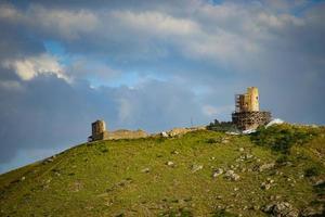 utsikt över genos fästning på sidan av ett berg med en molnig blå himmel i Krim foto