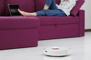 rengöring av robotrenare. flicka vilar hemma i soffan medan roboten dammsugar. koncept tid för dig själv. smart hus. modern tjej optimerar sin tid. robotar koncept. selektivt fokus. foto