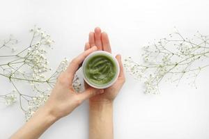 unga kvinnliga händer som håller en burk med grön naturlig kräm för ansikte eller kropp. ekologiska naturliga hudvårdsprodukter och blommor på vit bakgrund. förpackning av lotion eller grädde. skönhet kosmetisk hudvård koncept foto
