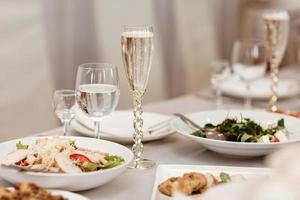 serveringsbord med en mängd läckra festmåltider och vin förberett för evenemangsfest eller bröllop. selektivt fokus foto