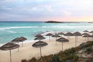 vackra halmparaplyer på stranden på den tomma stranden, ljusblått vatten och himmel, paradis tropisk strand, avkopplande tid, fantastisk utsikt, inga människor, solnedgångsbakgrund. selektivt fokus. foto