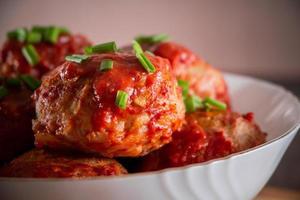 köttbullar med tomatsås och örter foto