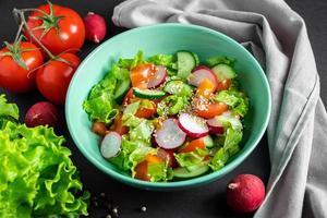 färsk grönsaksallad i en keramisk skål på grå bakgrund