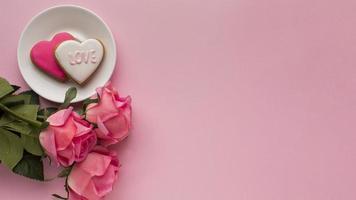 två hjärtformade kakor på rosa bakgrund foto