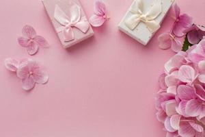rosa bakgrund med blommig kant och gåvor foto