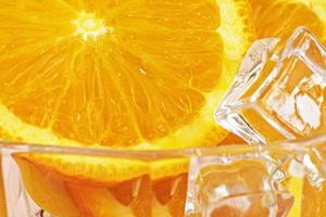 närbild av skivad färsk apelsin med isbitar på rosa bakgrund. foto
