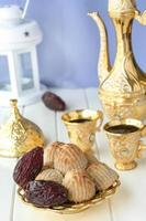 ramadankoncept. maamoul traditionell arabfylld bakelse eller kaka med dadlar eller nötter serveras med kaffe gyllene set. östra godis. närbild. vit trä bakgrund. foto