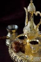 stilleben med traditionellt gyllene arabiskt kaffeset med dallah, kaffekanna och dadlar. mörk bakgrund. vertikalt foto