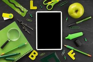 grön skolmaterialarrangemang med mock up-tablett på svart bakgrund foto