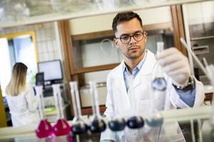 ung forskare som kontrollerar provrör foto