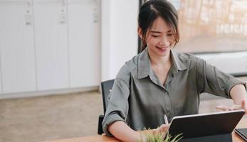 affärskvinnasammanträde vid ett skrivbord med en tablett foto