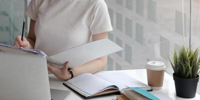 kvinna som skriver i ett bindemedel foto