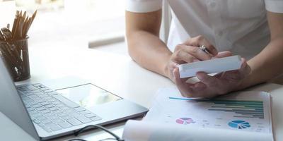 närbild av en person som använder en miniräknare vid ett skrivbord foto