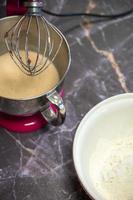 skål med mjöl bredvid en stor mixer på en mörk marmor bakgrund foto
