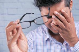 man tar bort glasögon för att gnugga huvudet på grund av huvudvärk foto