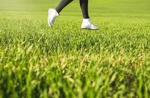 flickans fötter i vita sneakers som hoppar på en grön äng foto