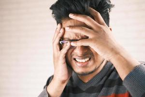man som lider av huvudvärk foto