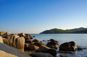 marinmålning med stenar på stranden och berg i bakgrunden vid Japans hav foto
