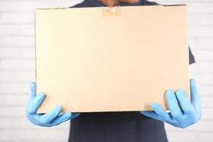 person som bär en låda med handskar på foto